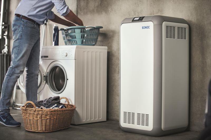 Ein Stromspeicher der Firma Senec steht in einer Waschküche, in der ein Mann die Waschmaschine bedient.