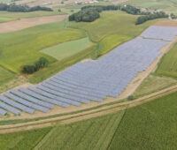 Auf einem leicht hügeligen, ansonsten landwirtschaftlich genutzten Gelände ist aus der Vogelperspektive eine langgestreckte, große Photovoltaik-Anlage zu sehen.