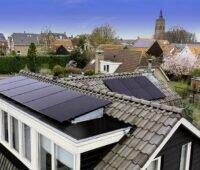 Haus mit Solarmodulen am Dach in einem Dorf mit Kirchturm.
