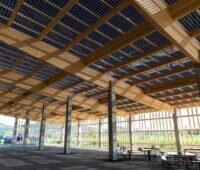 Ein Lagerdach mit Solarmodulen gedeckt, teils lichtdurchlässig, von innen