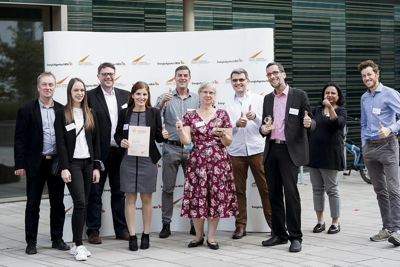 Preisträgerinnen und Preisträger freuen sich mit erhobenem Daumen vor einem Euroaolar-Transparent.