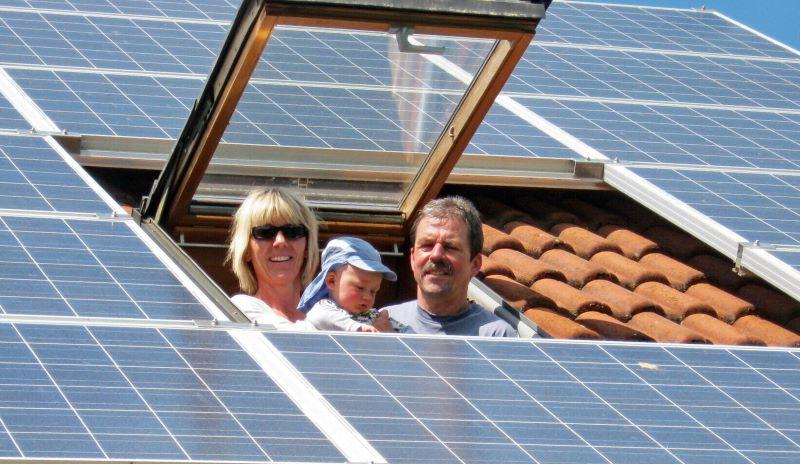 Eine Familie mit Baby blickt aus einem Dachfenster. Um sie herum ist das Dach mit Solarmodulen gedeckt.