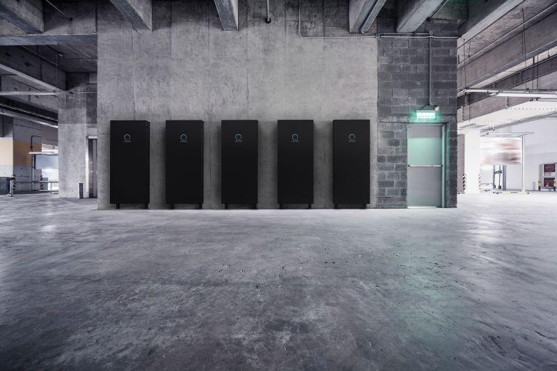In einer leergeräumten Fabrikhalle stehen fünf große schwarze Batteriespeicher an einer Wand.