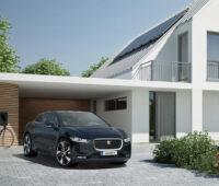 Im Vordergrund ein Elektrofahrzeug, links davon an einer Garage eine Ladestation, rechts ein weißes Haus mit Photovoltaikanlage