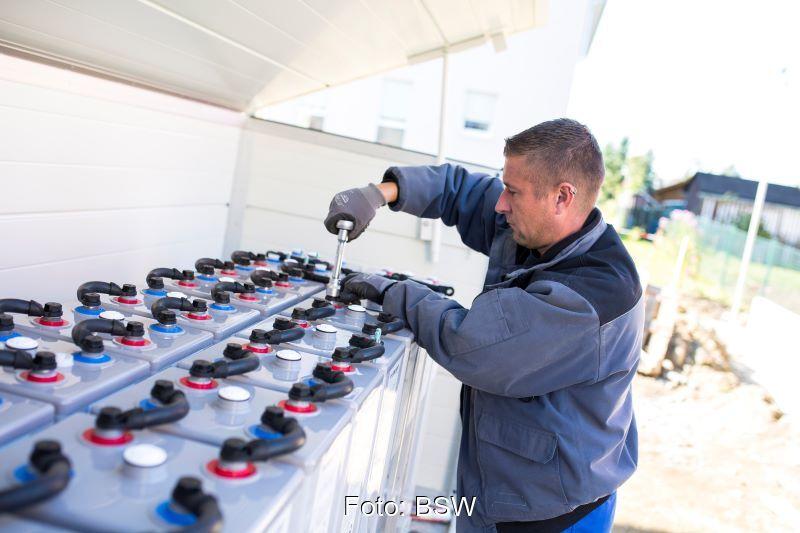 Ein Arbeiter prüft eine Batterieanlage.