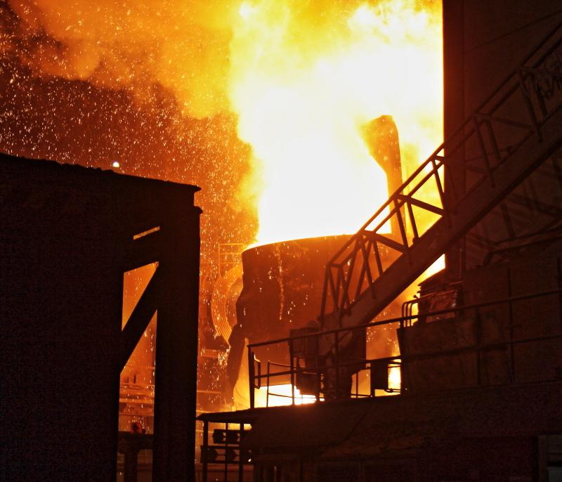 Ein Kessel mit glühendem Stahl im Stahlwerk, Funken sprühen