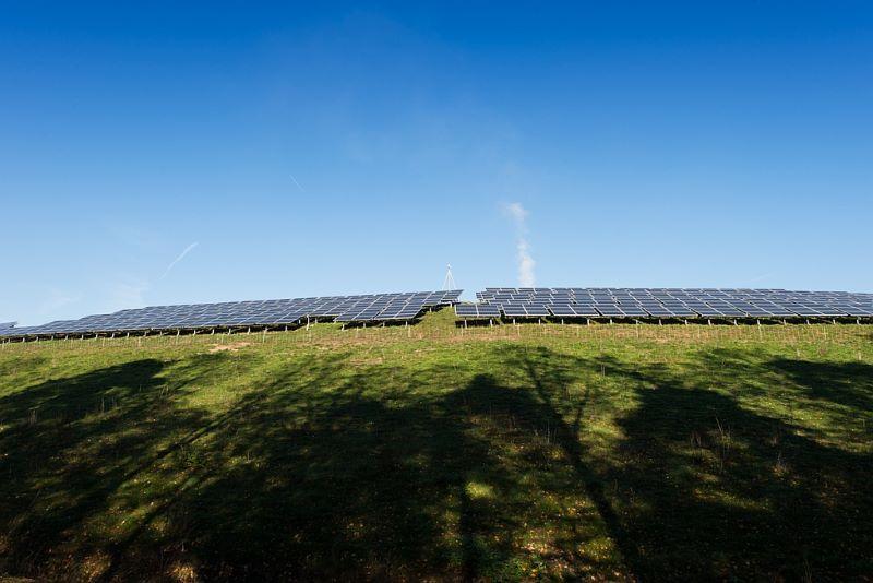 Ein Solarpark auf einem Hügel in der Ferne.