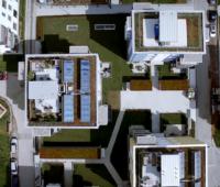 Luftaufnahme von Gebäuden mit Solarkollektoren auf den Dächern.