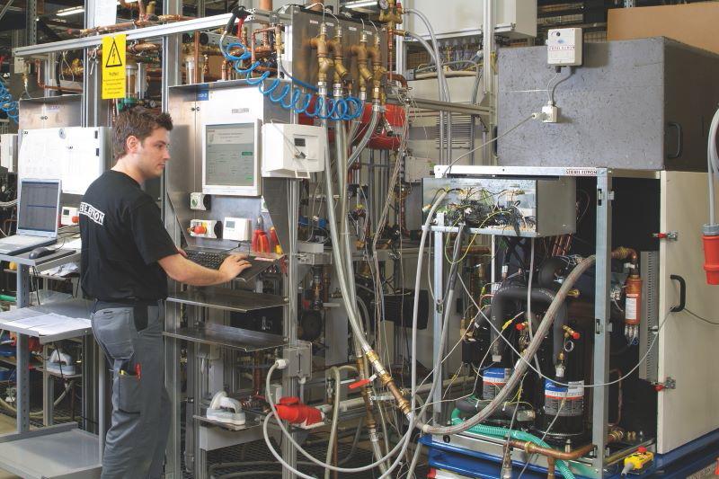 Mitarbeiter in einer Werkhalle prüft elektrisches Equipment