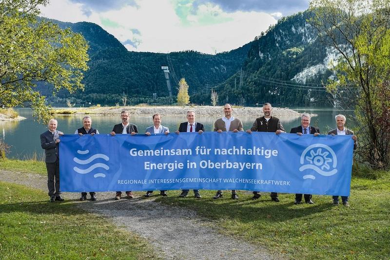 Männer mit blauem Banner vor Walchensee und Bergen, Wasserkraftwerk Walchensee