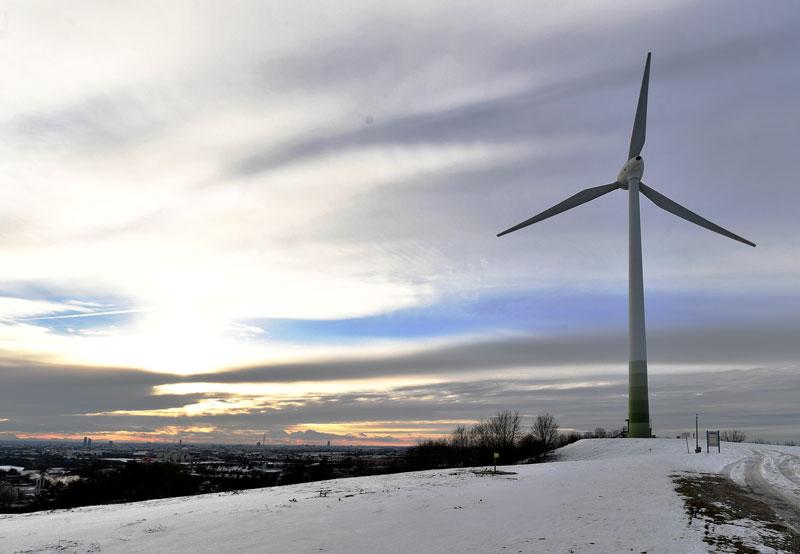 Windkraftwerk auf der ehemaligen Deponie in München-Fröttmaning mit Schnee und Sonnenuntergang