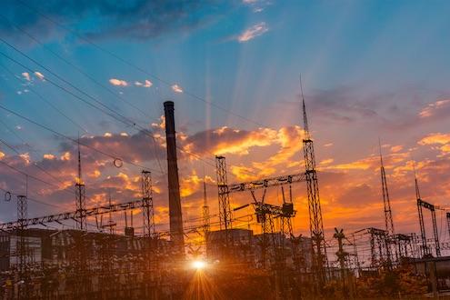 Sonnenuntergang hinter einer Trafostation und einem konventionellen Kraftwerk